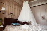 Svatební šaty visí nad postelí — Stock fotografie