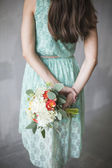 Wedding bouquet in a rustic style in the hands of the bride — Stock Photo