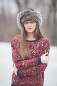 Beautiful girl in the park in winter, in a fur hat — Zdjęcie stockowe
