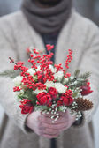 Man in the park in winter with a bouquet of red flowers — Stockfoto