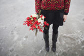 Beautiful girl in the park in winter,  with a bouquet of red flo — Zdjęcie stockowe