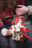 Woman and man in the park in winter with a bouquet of red flower — Stock Photo