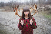 Woman in a park with horns — Stock Photo