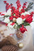 Winter wedding bouquet with pine cones and red and white flowers — Stock Photo