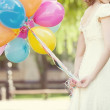 Bride with colored balloons in their hands — Stock Photo #9971591