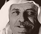Old photo with grain added, face of aged arabic man — Stock Photo