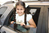 Little cute girl riding a car and looking through the window — Stock Photo
