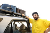 Młody człowiek preparating na wycieczkę, bagażu na dachu auta — Zdjęcie stockowe