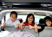 Smiling happy children in car with thumb up — Stock Photo