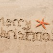 Merry Christmas written in the sand with star — Stock Photo