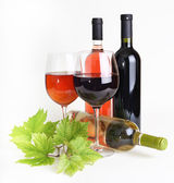 Wineglass, bottle of wine and grapes leaf — Stock Photo