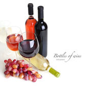 Wineglass, bottles of wine and grapes — Stock Photo