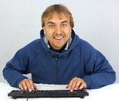 Taper sur le clavier et le sourire de l'homme — Photo