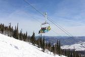 Sechs snowboarder fahren den lift vor dem hintergrund der berge — Stockfoto