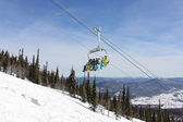 Six snowboarders ride the lift on a background of mountains — Стоковое фото
