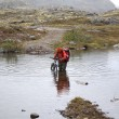 Crossing the river at a ford with a bicycle — Stock Photo
