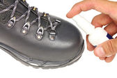 Processing trekking shoe with a protective spray — Stock Photo