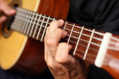Close up acoustic guitar in musician hands — Stock Photo