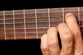 Hand, hold a chord on the guitar fretboard, vibrating string — Stock Photo