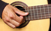 Human hand playing guitar — Stock Photo