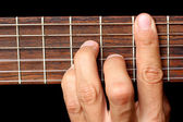 Hand holding a chord, and vibrating strings — Stock Photo