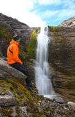 Girl sitting on a rock and looking at the beautiful waterfall — Stock Photo