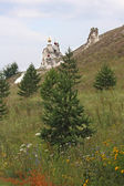 Orthodox cave temple, side view through small trees and flowers — Stock Photo