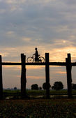 Silhouette of a cyclist on U Bein Bridge at sunset — Stock Photo