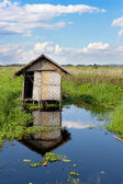 Abandoned house on stilts in the water — Stock Photo