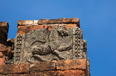 Old cracked bas-relief of lion on the facade of ancient temple — Stock Photo