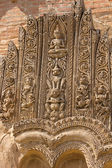 Old sloughing bas-relief with religious ornament on the facade o — Stock Photo