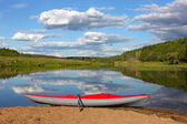 Red inflatable kayak on the sandy shore — Stock Photo