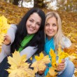Two happy young women in autumn forest — Stock Photo #12346214