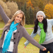 Two happy young women in autumn forest — Stock Photo