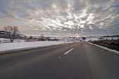 Road in winter with sun at sunset — Stock Photo