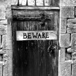 Stock Photo: Beware sign on an old wooden gate with spikes