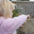 Two yaer old girl pointing out from a castle parapit — Foto Stock