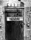 Beware sign on an old wooden gate with spikes — Stock Photo