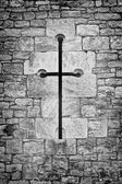 Christian crucifix or cross in the stone work of a chapel wall — Stock Photo