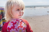 Young child on the beach in summer wearing flowery wetsuit — Foto Stock