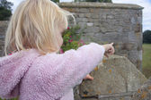 Two yaer old girl pointing out from a castle parapit — Stock Photo