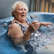 Stock Photo: Senior lady relaxing in a hot tub with champagne