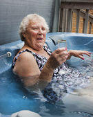 Senior lady relaxing in a hot tub with champagne — Stock Photo