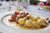Roast potatos with tomato and caper salsa and fish in background — Stock Photo