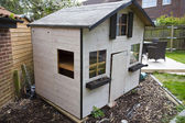 Wooden childrens garden playhouse or shed — Stock Photo