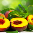 Ripe peaches with green leaves - Stock Photo