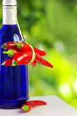 Bottle of alcohol and red chili peppers — Stock Photo