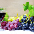 Glass of red wine with grapes on a table — 图库照片