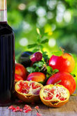 Red wine and pomegranates on table — Stock Photo