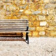 Wood bench against a brick wall — Stock Photo #14878191